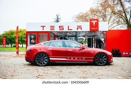 PARIS, FRANCE - NOV 29, 2014: New red Tesla Model S electric car in front of red showroom new car sale