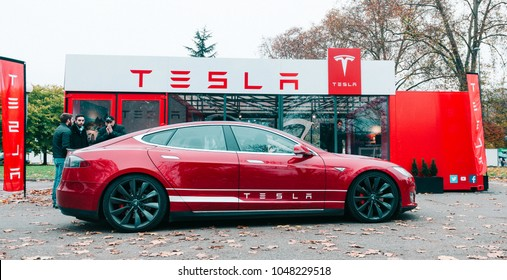PARIS, FRANCE - NOV 29, 2014: New Tesla Model S showroom parked in front of the red showroom with customers admiring the electric luxury car