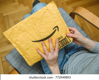 PARIS, FRANCE - NOV 4, 2017: Living room view from above of woman in armchair unpacking unboxing Amazon cardboard envelope with smile logotype printed