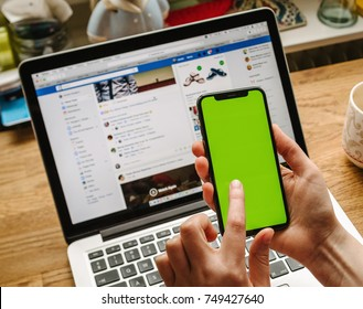 PARIS, FRANCE - NOV 5, 2017: POV of woman testing the new Apple iPhone X 10 smartphone (with Chroma Key Backgrounds) in creative room environment table  with Facebook Social network running on laptop