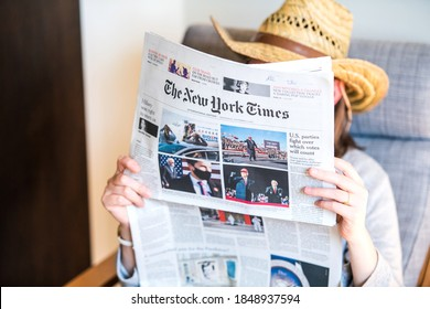 Paris, France - Nov 5, 2020: Woman reading in living room the latest newspaper The New york Times featuring on cover page the final day of election for U.S. President race between Donald Trump and Joe Biden