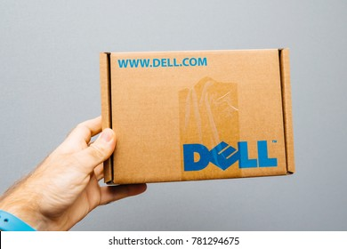 PARIS, FRANCE - NOV 6, 2017: IT service man holding against gray background cardboard box with DELL computer logo spare part inside for his IT department
