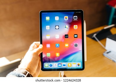 PARIS, FRANCE - NOV 7, 2018: Customer POV personal perspective experiencing new Apple iPad Pro with thin completely redesigned body and all apps on the home screen