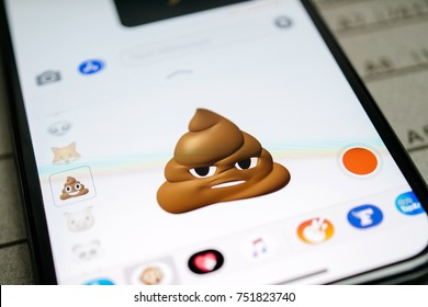 PARIS, FRANCE - NOV 9 2017: Poop 3d animoji emoji generated by Face ID facial recognition system with malicious face emotion close-up of the new iphone X 10 Display - tilt-shift lens used