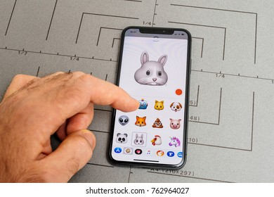 PARIS, FRANCE - NOV 9 2017: Man hand selecting sad rabbit animoji emoji generated by Face ID facial recognition system with malicious face emotion close-up of the new iphone X 10 Display