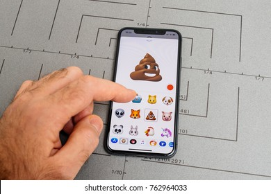 PARIS, FRANCE - NOV 9 2017: Man hand selecting Poop shit smiling animoji emoji generated by Face ID facial recognition system with malicious face emotion close-up of the new iphone X 10 Display