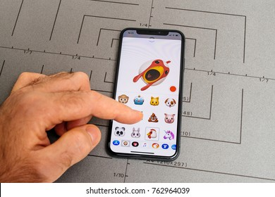 PARIS, FRANCE - NOV 9 2017: Man hand selecting singing rooster animoji emoji generated by Face ID facial recognition system with malicious face emotion close-up of the new iphone X 10 Display