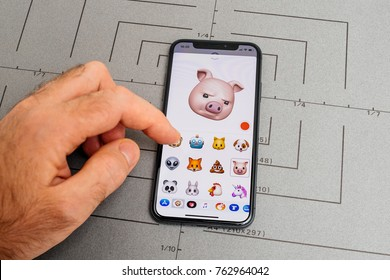 PARIS, FRANCE - NOV 9 2017: Man hand selecting suspicious Pig animoji emoji generated by Face ID facial recognition system with malicious face emotion close-up of the new iphone X 10 Display