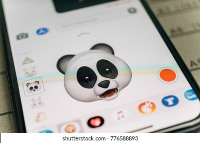 PARIS, FRANCE - NOV 9 2017: Panda bear 3d animoji emoji generated by Face ID facial recognition system with astonished face emotion close-up of the new iphone X 10 Display - tilt-shift lens used