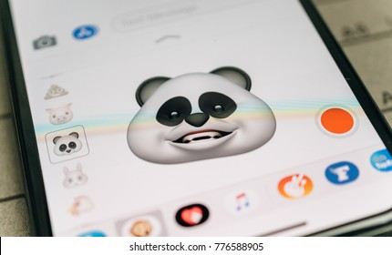PARIS, FRANCE - NOV 9 2017: Panda bear 3d animoji emoji generated by Face ID facial recognition system with smiling face emotion close-up of the new iphone X 10 Display - tilt-shift lens used