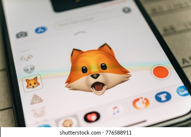 PARIS, FRANCE - NOV 9 2017: Fox animal 3d animoji emoji generated by Face ID facial recognition system with wow astonished face emotion close-up of the new iphone X 10 Display - tilt-shift lens used