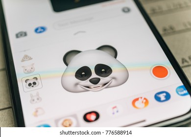 PARIS, FRANCE - NOV 9 2017: Panda bear 3d animoji emoji generated by Face ID facial recognition system with large smile face emotion close-up of the new iphone X 10 Display - tilt-shift lens used