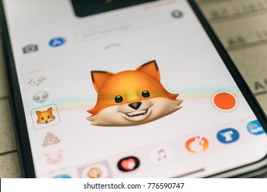 PARIS, FRANCE - NOV 9 2017: Fox animal 3d animoji emoji generated by Face ID facial recognition system with happy face emotion close-up of the new iphone X 10 Display - tilt-shift lens used