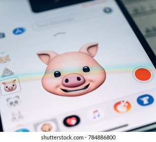PARIS, FRANCE - NOV 9 2017: Pig animal 3d animoji emoji generated by Face ID facial recognition system with happy smile face emotion close-up of the new iphone X 10 Display - tilt-shift lens used