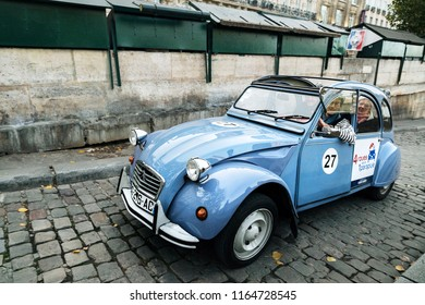Paris, France - November 01, 2017: Tourist retro car Citroen 2cv of heavenly color carries tourists along the Seine river embankment and evening, autumn Paris. Smiling tourists and Parisians