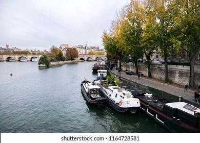 "Paris, France - November 01, 2017: Autumn embankment of the river Seine. Boats tied up on Seine River. Autumn city landscape. Manned barges are moored to the coast. Ile de la Cite ""Island of Paris"""