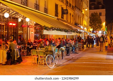 PARIS, FRANCE - NOVEMBER 09, 2018: People at a street restaurant in Paris at night. Paris is the most visited city in Europe