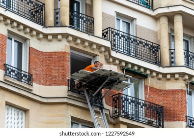 PARIS, FRANCE - NOVEMBER 10, 2018: Typical Parisian moving house. Relocation service man lifting and entering  boxes to apartment through window.