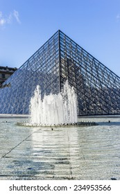 PARIS, FRANCE - NOVEMBER 12, 2014: View of pyramid and fountain at courtyard of Louvre Museum. Louvre Museum is one of the largest and most visited museums worldwide.