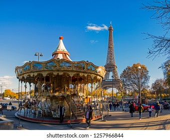 Paris, France - November 13, 2018: Eiffel Tower with merry go round from Trocadero at sunny day. Vintage colorful carousel and Tour Eiffel
