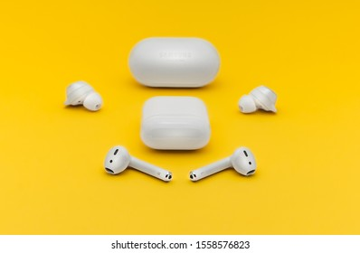 Paris, France - November 13, 2019: Apple AirPods next to Samsung Bluetooth Earbuds wireless headphones isolated on yellow background. Studio shot with copy space.