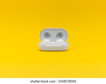 Paris, France - November 13, 2019: The new Samsung Bluetooth Earbuds wireless headphones isolated on yellow background. Studio shot with copy space.