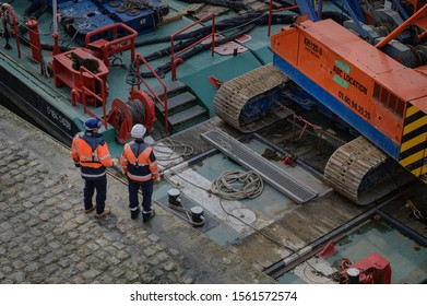 PARIS, FRANCE - NOVEMBER 13, 2019 : Workers and a mobile crane on a barge during civil-engineering works in the Bastille Harbour. Overhead shot with lots of technical equipment in the frame.