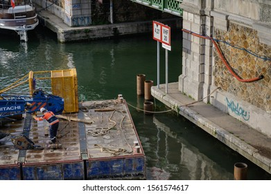 PARIS, FRANCE - NOVEMBER 13, 2019 : Workers and a mobile crane on a barge during civil-engineering works in the Bastille Harbour. Sign with the radio frequency of the harbour in the frame.