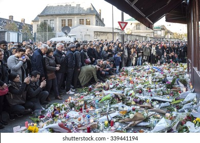 PARIS, FRANCE - NOVEMBER 14, 2015 :  People in front of the Bar Hotel Le Carillon street Alliber in tribute to victims of the Nov. 13, 2015 terrorist attack in Paris at the Bataclan.