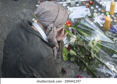 PARIS, FRANCE - NOVEMBER 14, 2015 :  A woman pray in front of the restaurant Le Petit Cambodge street Alliber in tribute to victims of the Nov. 13, 2015 terrorist attack in Paris at the Bataclan.