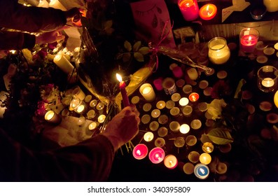 PARIS, FRANCE - NOVEMBER 14, 2015: People lighting candles in memory of the victims of the November 13 terror attacks in Paris at Republic Square.