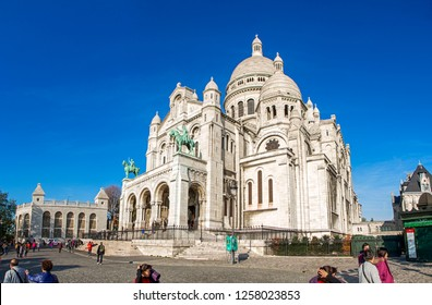Paris, France - November 14, 2018: Tourists walking near Sacre Coeur Basilica entrance also known as Basilica of Sacred Heart. Situated in Montmartre which is the highest 130 meters hill in Paris