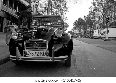 Paris, France - November 14, 2018: Vintage 2CV Charleston van 1983 parked on the city street. Citroen driver opened the door. Low angle view. Black and white photography