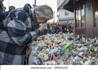 PARIS, FRANCE - NOVEMBER 15, 2015 :  An old woman very touched in front of the bar hotel Le Carillon near the theater Bataclan after the terrorist attack in Paris, November 13, 2015.