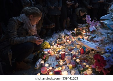 PARIS, FRANCE - NOVEMBER 15, 2015 :  A woman lights a candle in front of the theater Le Bataclan in tribute to victims of the Nov. 13, 2015 terrorist attack in Paris at the Bataclan.