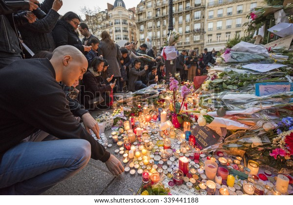 PARIS, FRANCE - NOVEMBER 15, 2015 :  A man lights a candle in front of the theater Le Bataclan in tribute to victims of the Nov. 13, 2015 terrorist attack in Paris at the Bataclan.