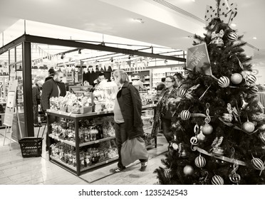 PARIS, FRANCE - NOVEMBER 17, 2018: People choosing delicious sweets, chocolates and teas at gourmet  grocery of BHV Marais department store decorated for Christmas.  Sepia photo.