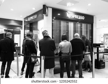 PARIS, FRANCE - NOVEMBER 17, 2018:  People buy Nespresso coffee capsules at vending machine in BHV Marais department store. Nestle Nespresso is part of Nestle Group based in Switzerland. Black white.