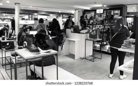 PARIS, FRANCE - NOVEMBER 17, 2018: People shopping in UGG store in BHV Marais department store. UGG is an American footwear company best known for its sheepskin boots. Black and white photo.