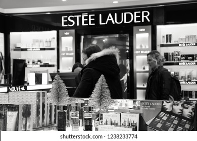 PARIS, FRANCE - NOVEMBER 17, 2018:  Women shop at Estee Lauder counter in BHV Marais department store. Estee Lauder company known for makeup, fragrance, skin and hair care products. Black white photo.