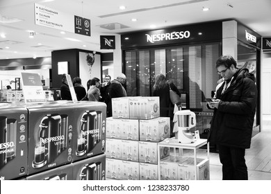 PARIS, FRANCE - NOVEMBER 17, 2018:  People shopping at kitchen electric appliances at buy Nespresso coffee capsules at vending machine in BHV Marais department store. Black and white photo.