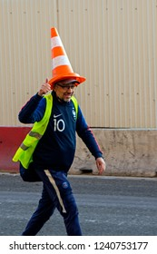 Paris, France - November 17, 2018: Demonstrant in yellow waistcoat and with plastic street cone on head demonstrate during a strike against the fuel price increase