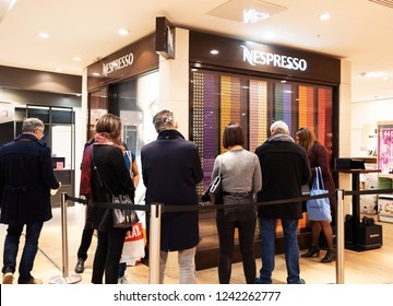 PARIS, FRANCE - NOVEMBER 17, 2018:  People buying Nespresso coffee capsules at vending machine in BHV Marais department store. Nestle Nespresso is part of Nestle Group based in Switzerland.
