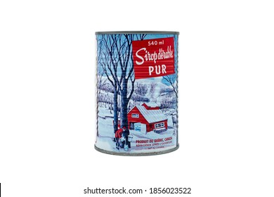 PARIS, FRANCE - NOVEMBER 17, 2020: Pure Maple Canadian Syrup metal can with an vintage illustration of the traditional method to collect maple sap, isolated on a white background. Text in french.