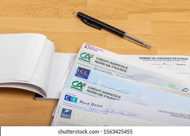 Paris, France - November 18, 2019 : Checks of different french banks set on a wooden desk. France is the European country where checks are most used