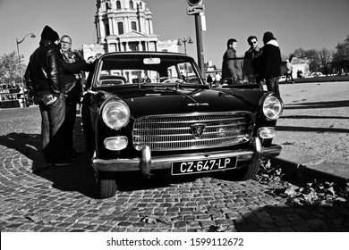 Paris, France - November 18th 2018 : Black Peugeot 404 parked on the street, with people.  Each sunday, an association of cars organise an exhibition in front of the Army Museum, the Invalides.