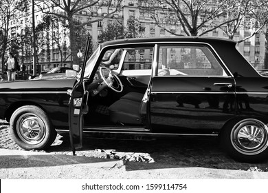 Paris, France - November 18th 2018 : Black Peugeot 404 parked on the street, with a door open (side view). There's the driver place, two seats and the steering wheel.