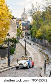 Paris, France - November 19, 2017: Driving the small streets of Montmartre on board a hired vintage french car with driver is a very popular way for tourists to explore the districts of Paris.