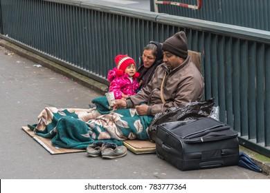 Paris, France, November 2017 - Homeless family sitting on the street