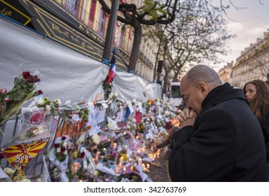 PARIS, FRANCE - NOVEMBER 23, 2015 :  A man pray in front of the theater Le Bataclan in tribute to victims of the Nov. 13, 2015 terrorist attack in Paris at the Bataclan.